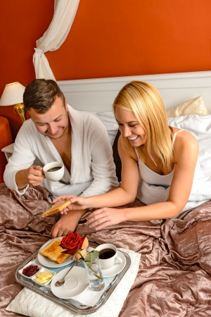 Eating romantic breakfast in bed smiling couple Valentines day photo