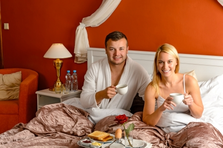 Sitting happy husband wife bed drinking tea romantic hotel breakfast photo