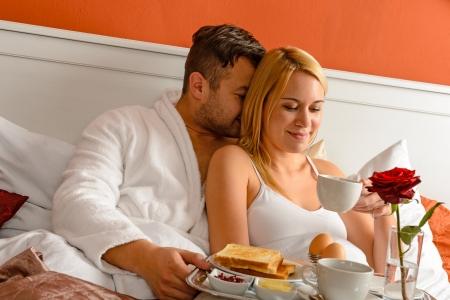 desayuno romantico: Caricias ma�ana joven pareja rom�ntica en el caf� cama potable Foto de archivo