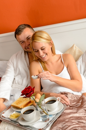 romantic room: Happy lovers lying bed eating romantic breakfast together morning