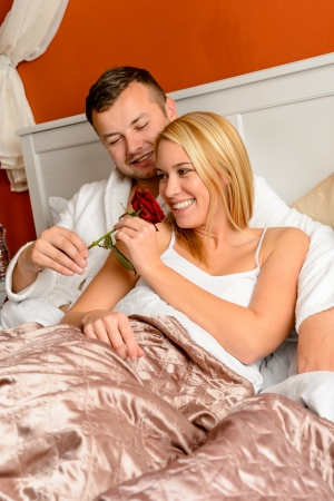 Happy couple lying bed smelling rose romantic Valentine's day Stock Photo - 17887249