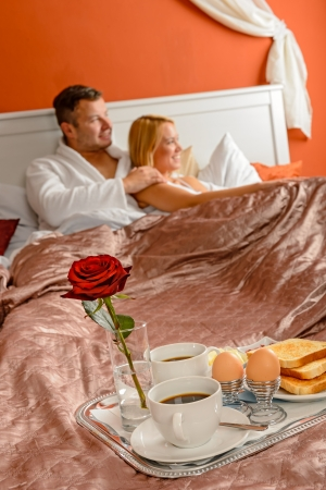 Romantic breakfast hotel room service young couple watching bed photo