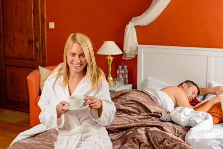 Young woman sitting bed drinking boyfriend sleeping hotel room Stock Photo