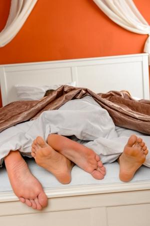 pies masculinos: Pareja acostada cama descalza bajo los pies de edredón