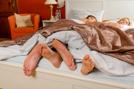 poking: Lovers foot poking out bed covers sleeping couple