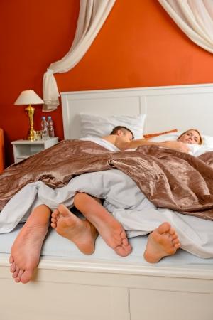 pies masculinos: Dormir pareja descalzo acostado lado de la habitación al lado de la cama Foto de archivo