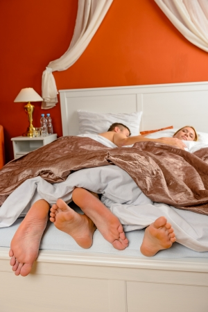 feet in bed: Sleeping couple barefoot lying bed room side by side