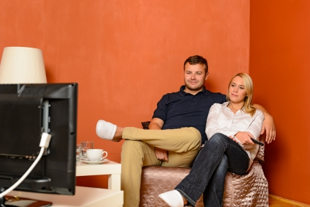 Young couple watching tv cuddling sitting armchair living room photo