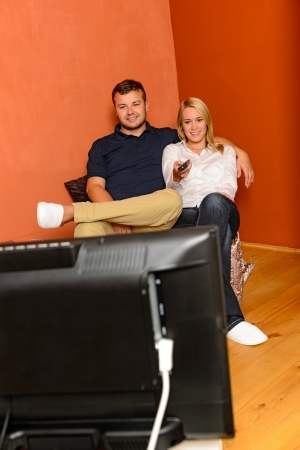 Smiling couple changing channels watching television evening using remote control Stock Photo - 17887291