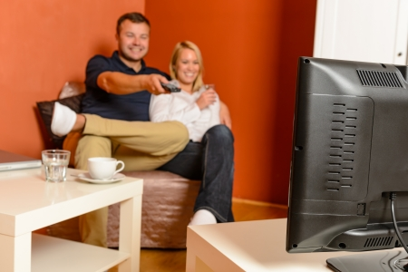 Happy couple watching tv evening relaxing changing channels remote control Stock Photo - 17887292