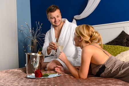 Lovers clinking champagne glasses in bed enjoying anniversary hotel room photo