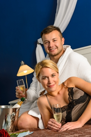 Intimate affair bed young couple drinking champagne woman nightgown photo