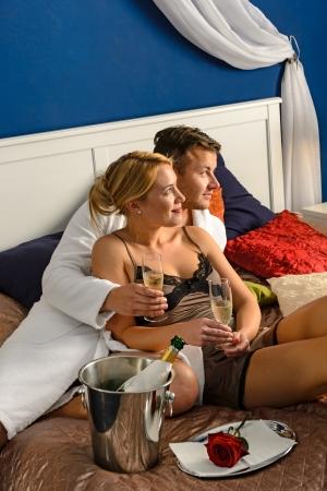 anniversary sexy: Romantic couple cuddling bed drinking champagne celebrating honeymoon hotel Stock Photo