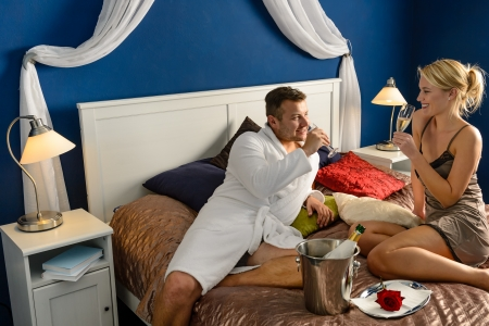 Romantic hotel room young couple sexy nightgown robe drinking champagne photo