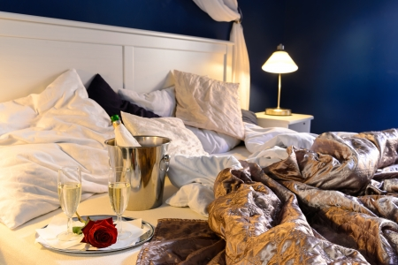 Romantic bedroom rumpled covers luxury hotel champagne bucket photo