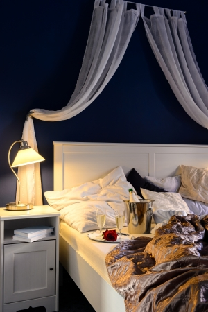 Empty unmade luxury bed romantic feeling with champagne photo