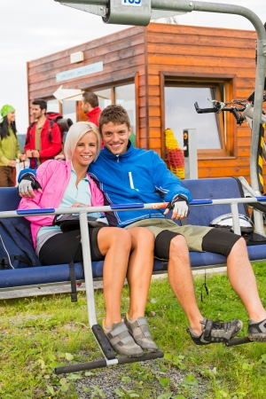 sweatsuit: Smiling hugging couple sitting and waiting on chair-lift Stock Photo