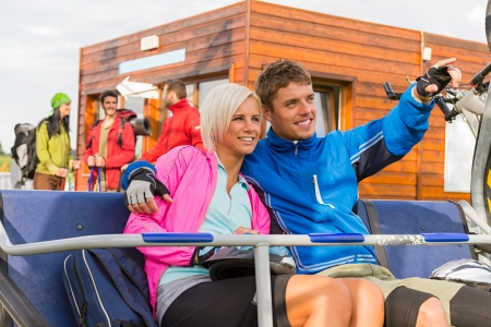Cheerful couple sitting on chair lift man pointing photo