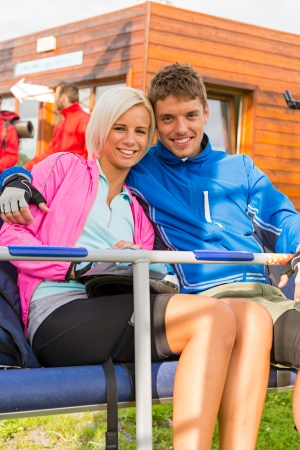 Smiling young couple sitting together on char lift Stock Photo - 18599086