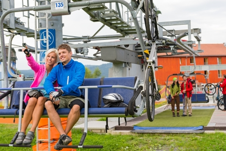 Happy couple traveling by chair lift enjoying landscape Stock Photo - 18600760