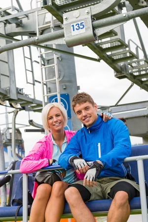 sweatsuit: Smiling couple in sweatsuit sitting on char lift in springtime