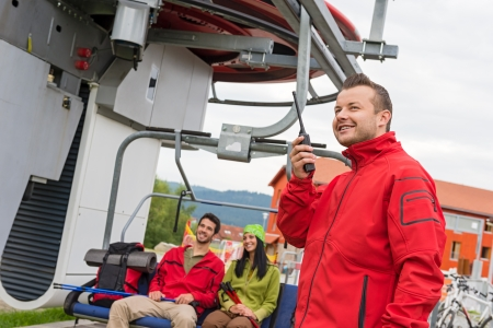Man in red coat using radio starting chair lift Stock Photo - 18599052