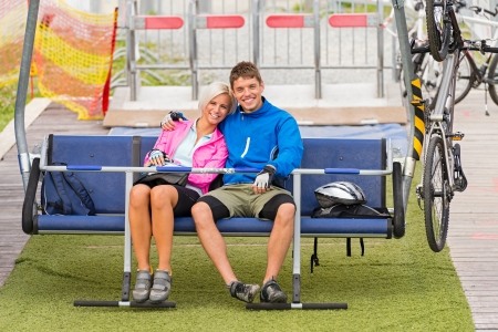sweatsuit: Cuddling happy couple sitting on chair lift with bicycles