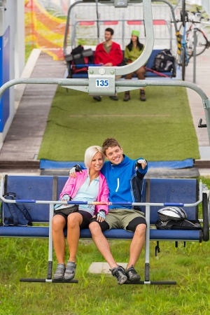 sweatsuit: Cuddling couple pointing on chair lift in sweatsuits Stock Photo