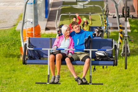 cableway: Couple on chair lift enjoying landscape Stock Photo