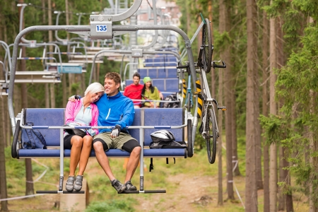 Carefree couple traveling by chair lift with bicycle Stock Photo - 18599446