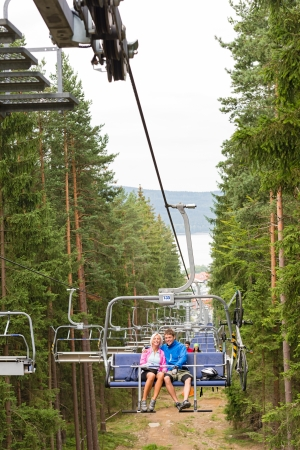 Young couple sitting on chair lift traveling through forest Stock Photo - 18600839