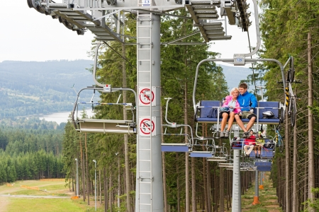 sweatsuit: Cuddling couple going through pinewood by chair lift