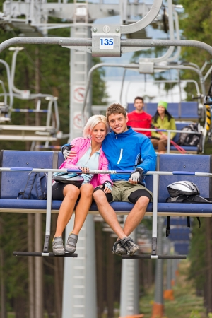 Cuddling young couple sitting on chair lift in the pinewood Stock Photo - 18599257