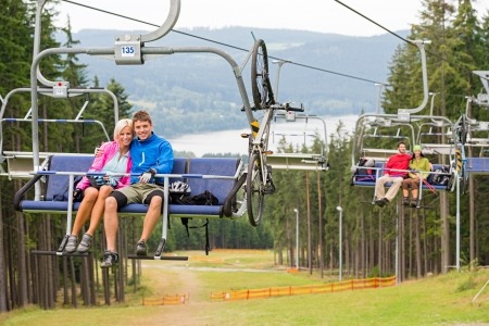 Smiling couples using chair lift in scenic landscape Stock Photo - 18599382