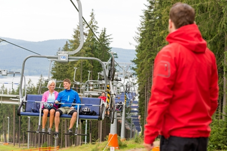 sweatsuit: Young couple enjoying chair lift in the wood holiday resort