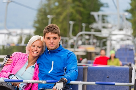 lipno: Hugging young couple in sweatsuits sitting on chair lift Stock Photo