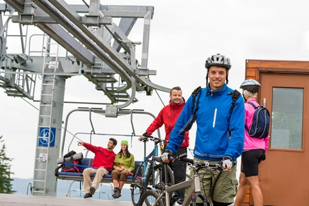 Sporty couple getting on bicycles after chair lift trip Stock Photo - 18599167