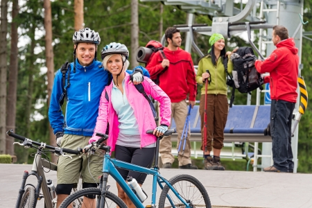Smiling mountain bikes couple and hikers waiting after chair lift trip photo
