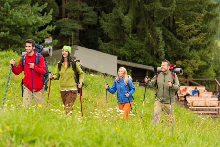 lipno: Smiling young people trekking in nature landscape with sticks