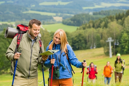 lipno: Young hiking couple with friends looking map to find track Stock Photo