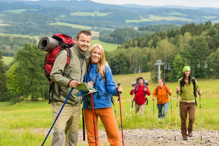 Smiling couple posing with hiking sticks and map on track photo