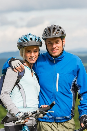sweatsuit: Young smiling sporty couple with bicycles in helmet Stock Photo