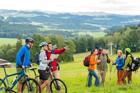 Hikers helping cyclists following track in nature landscape