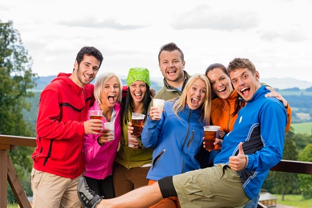 Smiling young people posing with beer and landscape background