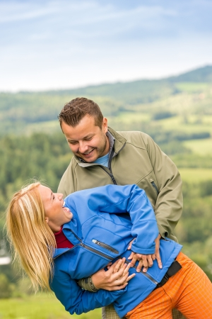 lipno: Sporty young couple hugging in front of scenic landscape Stock Photo