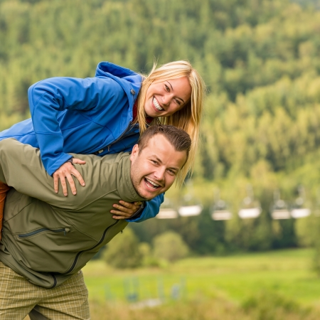 Young smiling couple having fun piggyback riding in the nature photo