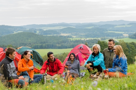 lipno: Smiling young people enjoying nature beside tents and scenic view
