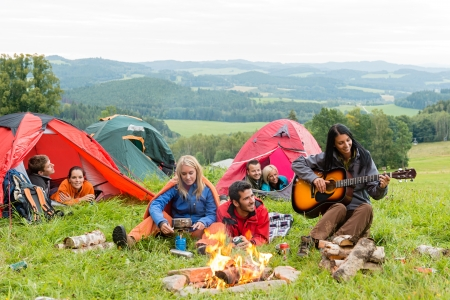girl playing guitar: Campers in tents listening to girl playing guitar beside campfire