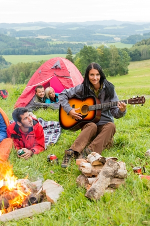 Young woman playing guitar beside camping friends lying in tents photo