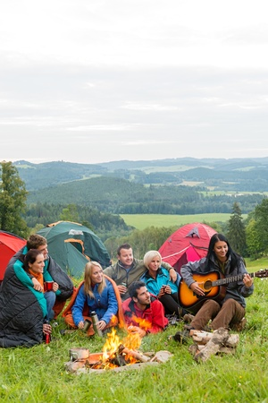 Group of friends sitting beside tents, campfire girl playing guitar Stock Photo